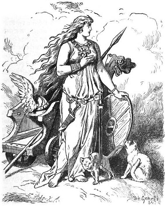A black-and-white illustration of Freyja standing beside her chariot with her cats, wearing Brisingamen, carrying a knife and spear and shield, with her helmet sitting beside her