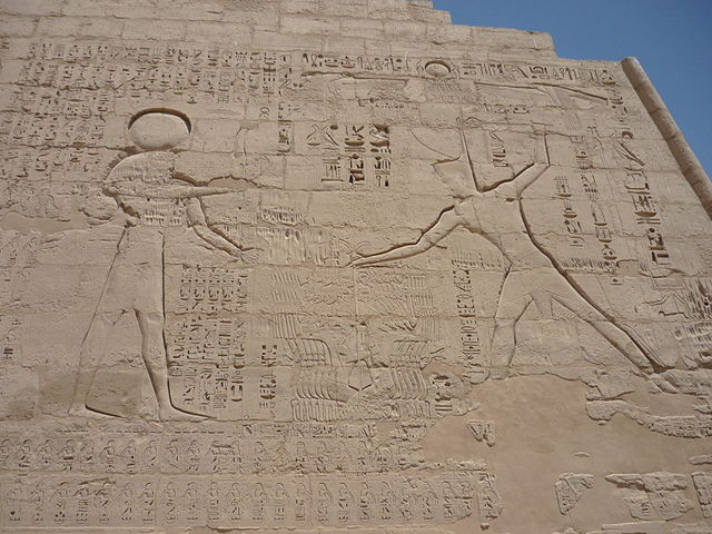 An ancient Egyptian stone wall relief depicting the sun god Ra on the left with a falcon's head and a sun disc above it, holding arms out toward the pharaoh Ramesses III, crowned, on the other side