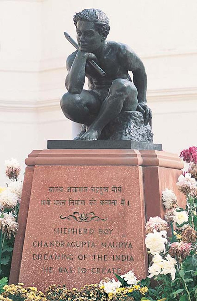 """A bronze statue of a naked young boy with a flute sitting contemplatively on a stone; the legend on the plinth below says, """"Shepherd boy Chandragupta Maurya dreaming of the India he was to create"""""""