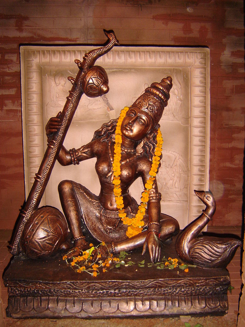 A wooden statue of the Hindu goddess Sarasvati, wearing a skirt and crown, holding her veena and accompanied by her swan, garlanded with flowers