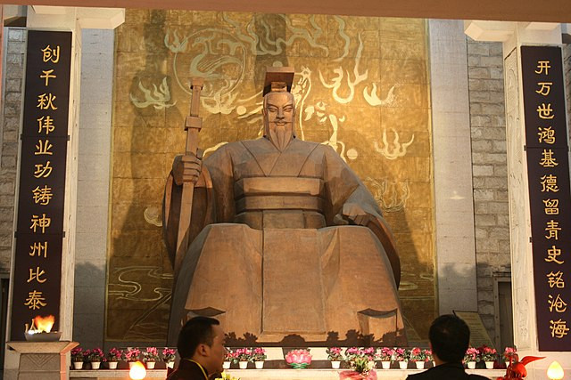 A huge stone statue of the Chinese emperor Huang Di, sitting before a golden backdrop with artwork of flames, holding a sword and wearing the crown of office; in front of him, two men look up