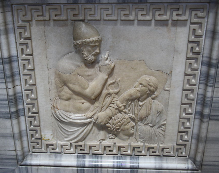 A white marble relief of Hephaistos in a cap holding up a finger against the gods looking up at him, accompanied by Dionysos wearing a wreath of leaves