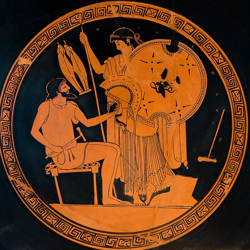 An orange Greek pottery vase depicting a seated Hephaistos holding a hammer and the helmet he is making for Akhilles, while the sea nymph Thetis stands over him holding a shield and spear