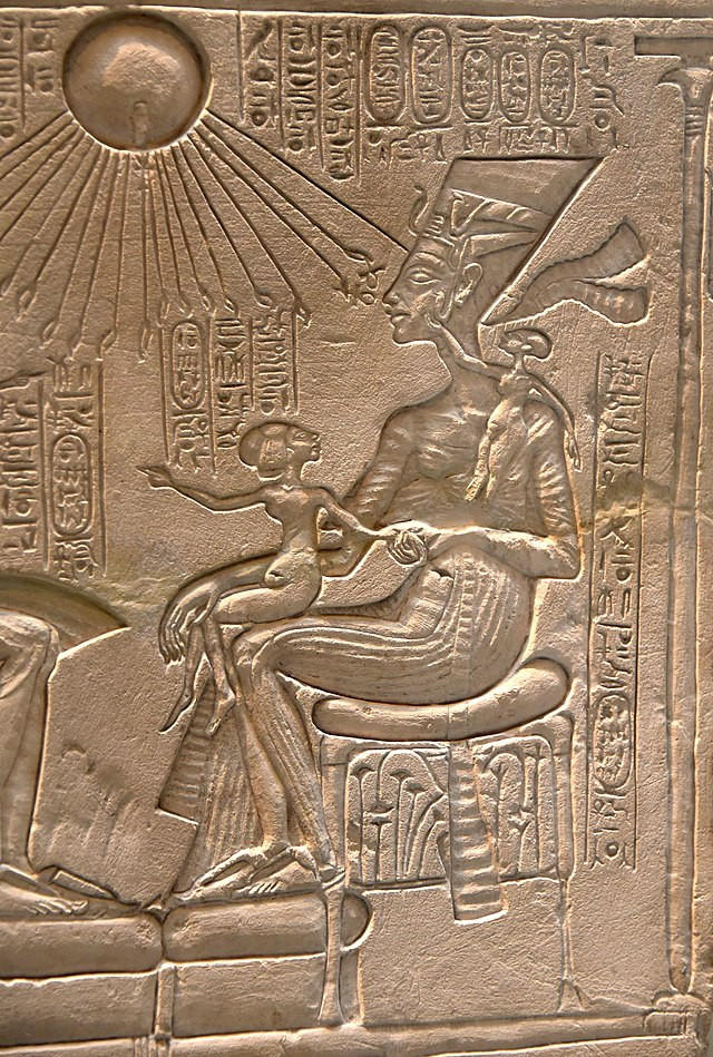 A stone relief of the ancient Egyptian god Aten, represented as a sun disc with many rays with hands on the end reaching down from the sky; beneath, Nefertiti and her children worship him