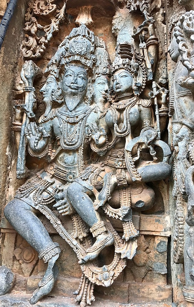A three-dimensional wall relief from a 12th-century temple depicting the Hindu deities Brahma and Sarasvati, both wearing full regalia, crowns, and jewelry, holding their hands up in blessing while Sarasvati sits in Brahma's lap