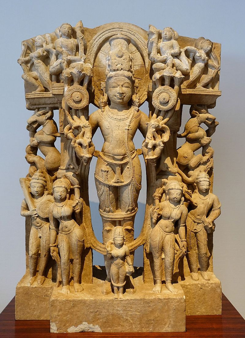 A weathered stone statue of Surya crowned with the sun, surrounded by smaller figures representing his wives, children, and followers