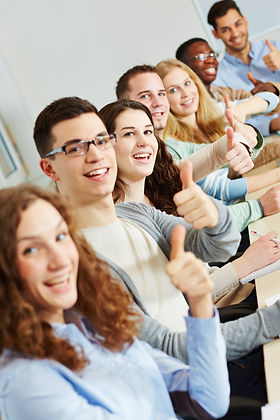 Many happy successful students holding t