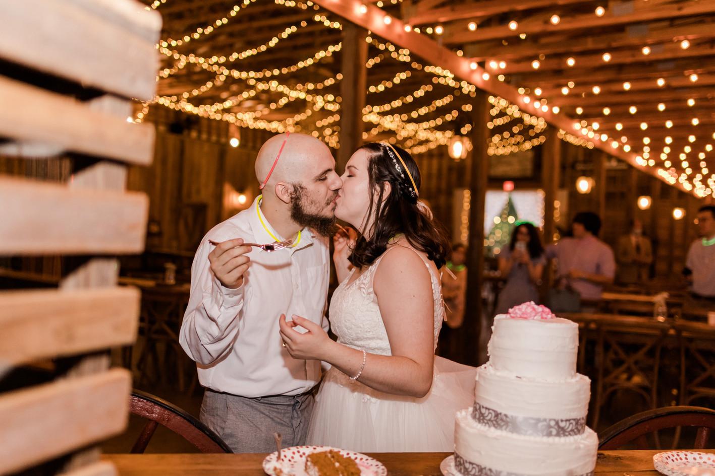 Clara & John kissing by cake