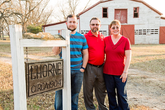 Jeremy, Jim and Anna at the L'Horne sign in front of the old barn