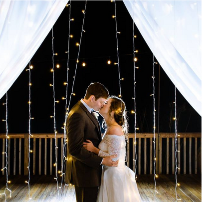 Kiss with curtain lights around them