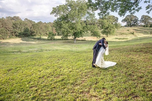 Kiss with hills in background |The Wedding Barn at L'Horne