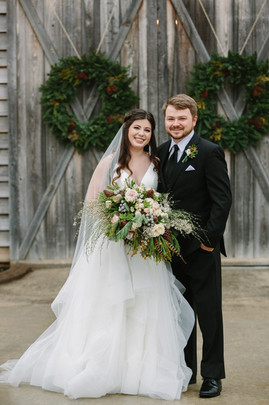 happy couple in front of barn