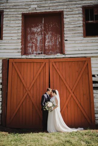 Caroline & Brett in front of red doors