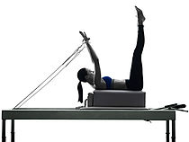 Woman using a Pilates Reformer machine at Get Moving Exercise Physiologist