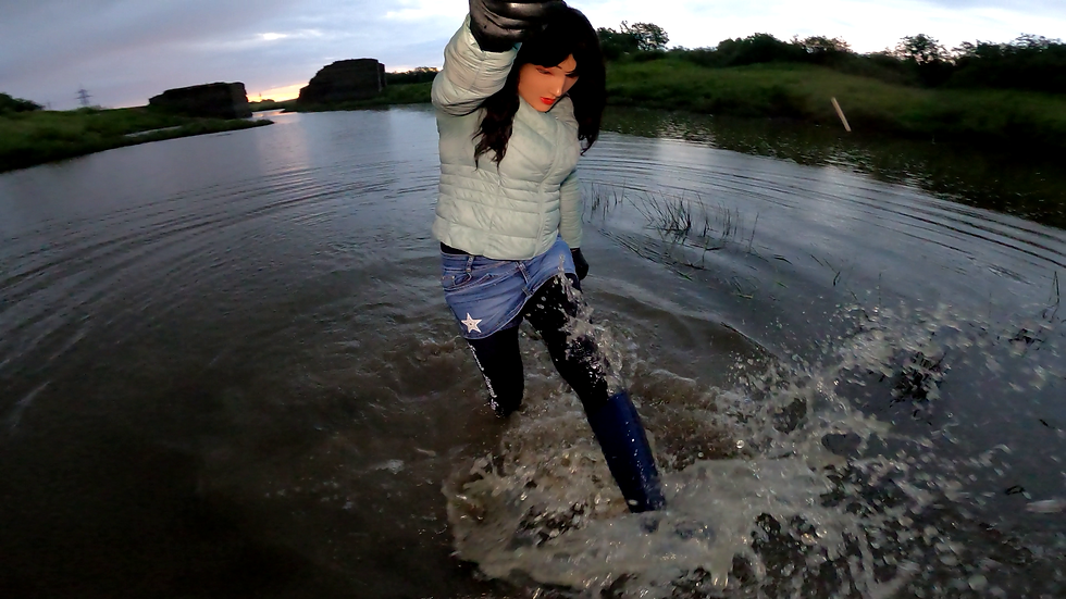 Girl in a skirt and rubber boots in the water
