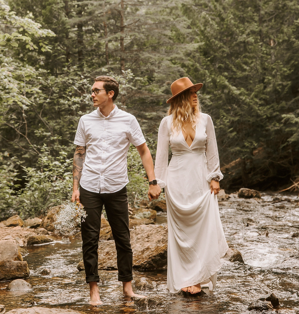 Bride wearing a brown hat and groom holding a wildflower bouquet standing in a Michigan river holding hands