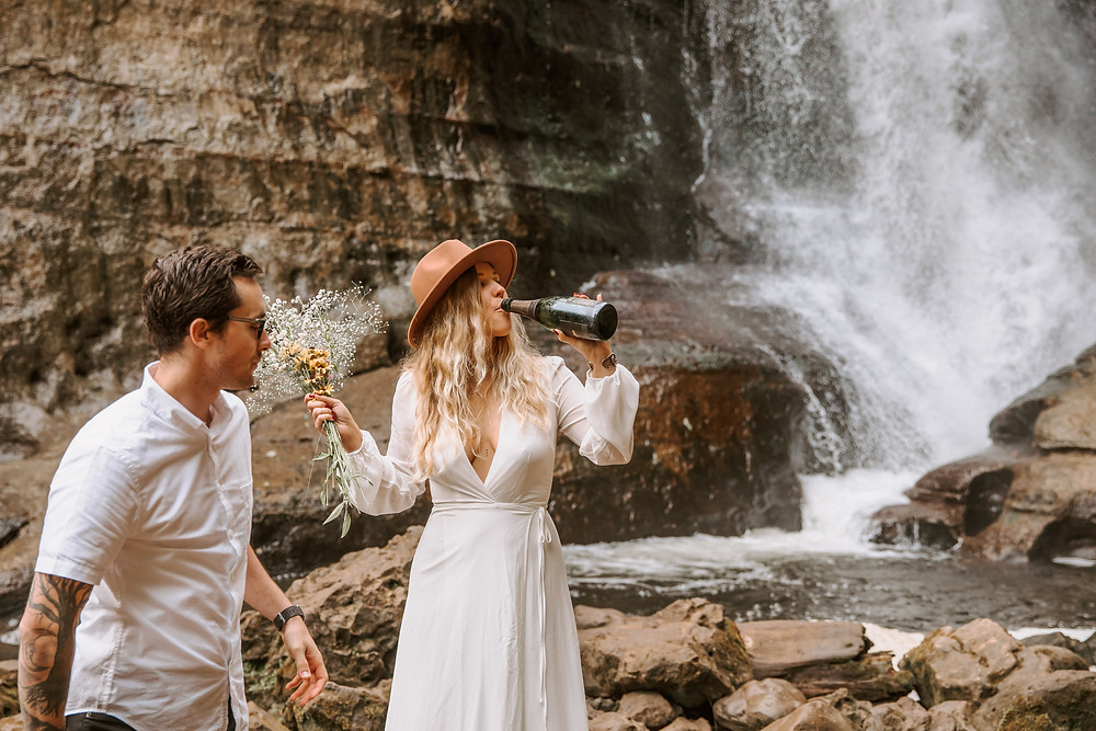 Bride and groom drinking champagne after their elopement in Miners Falls Michigan.