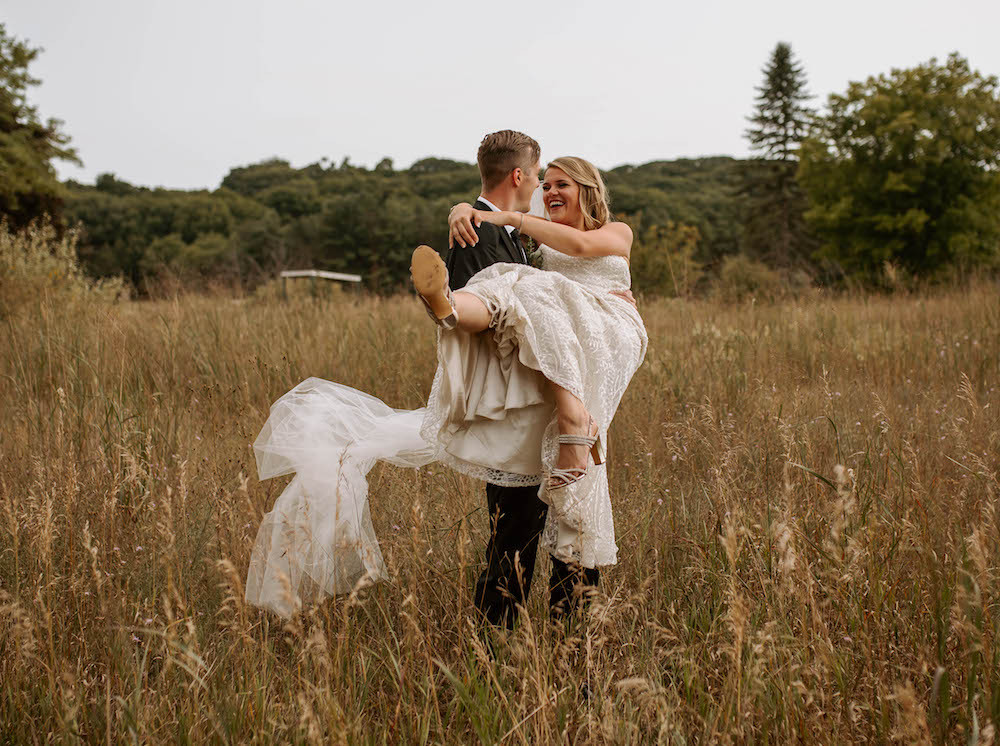 Bride and groom portraits in a field captured by Andi B Photo.