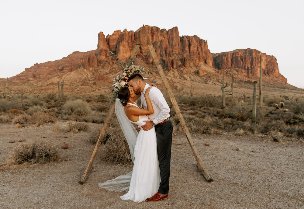 Bride and groom kissing in front of their A-frame arch in the middle of the Arizona desert after their elopement.