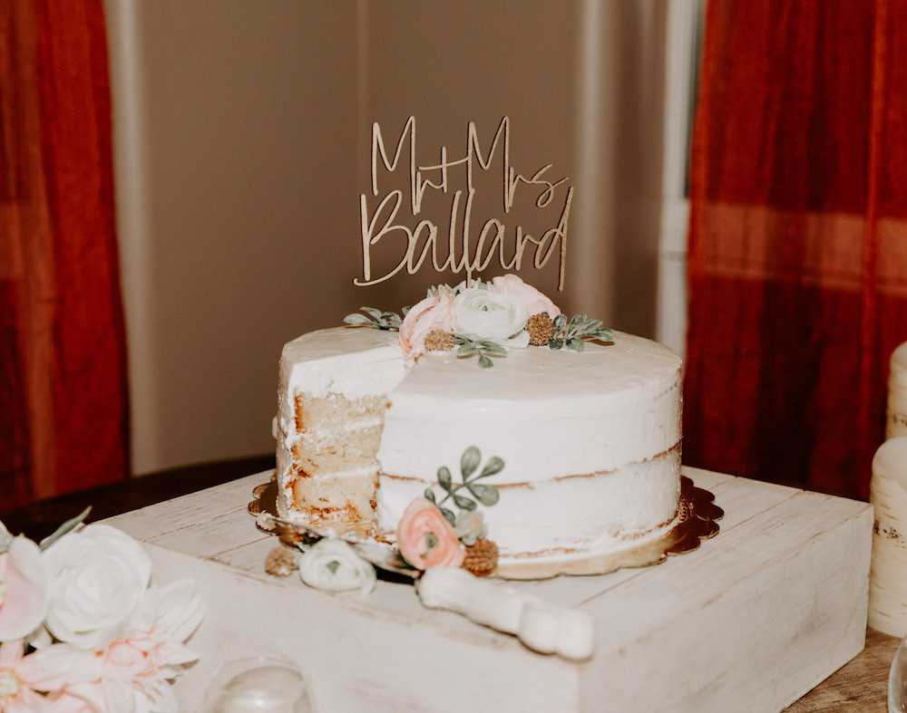 White buttercream wedding cake with a slice taken out and a custom last name cake topper.