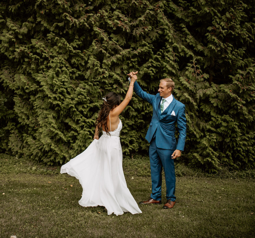 Groom in a blue tuxedo twirling the bride on their wedding day.