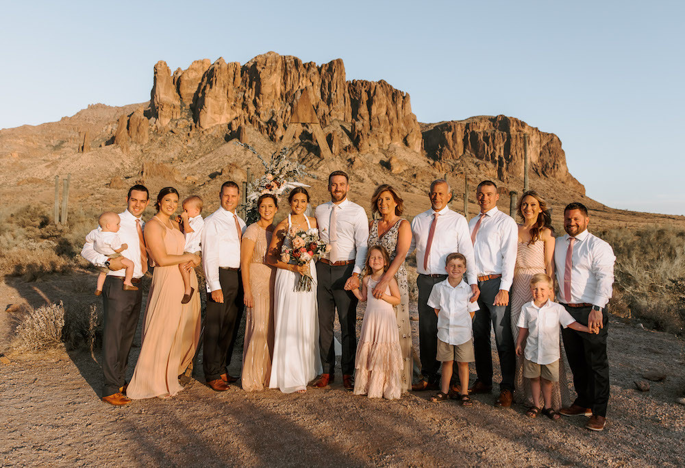 Bride and groom with their family standing in front of the Superstition Mountains in Arizona.