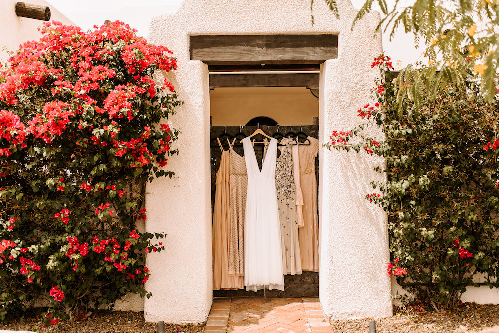 Wedding dress and bridesmaid dresses hanging in the doorway of a white desert themed Airbnb in Scottsdale, AZ.