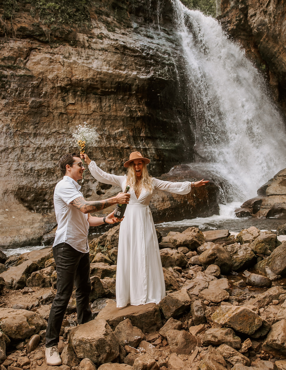 Bride and groom opening a bottle of champagne in front of a waterfall after their elopement.