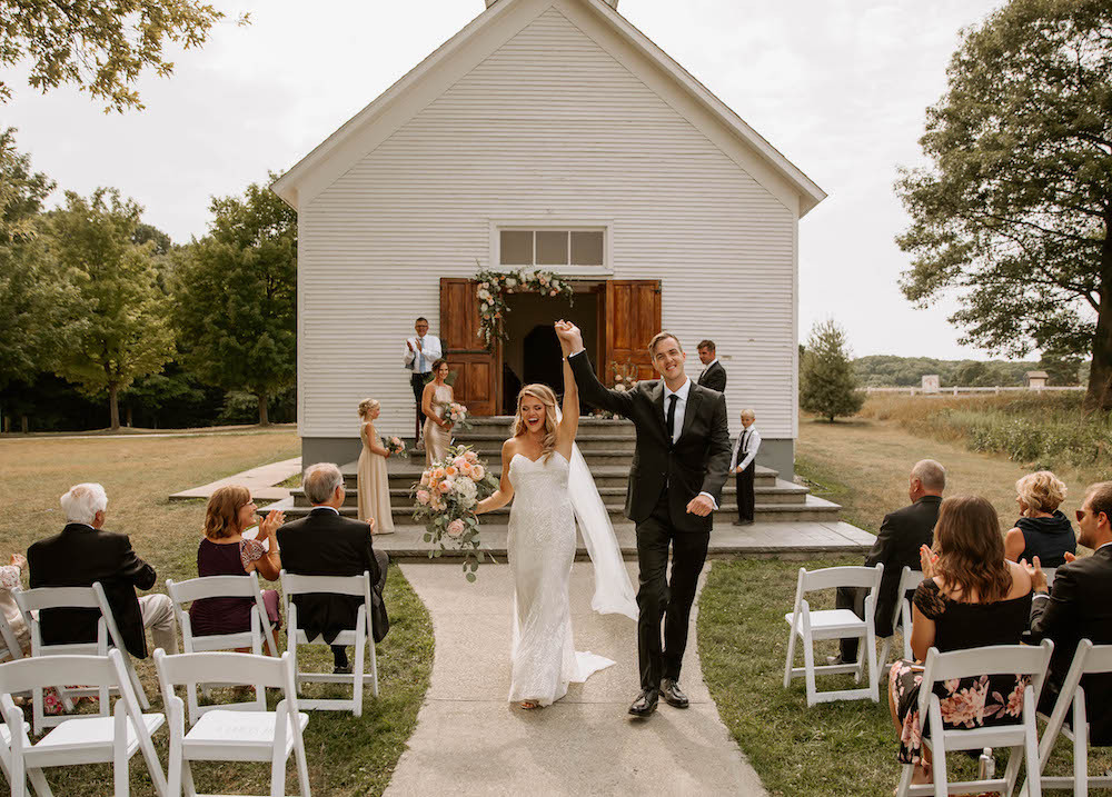 Bride and groom walking down the aisle together after getting married.