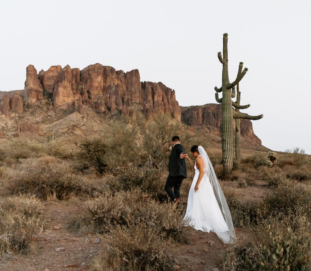 Bride and groom walking through Lost Dutchman State Park, Arizona for their desert elopement.