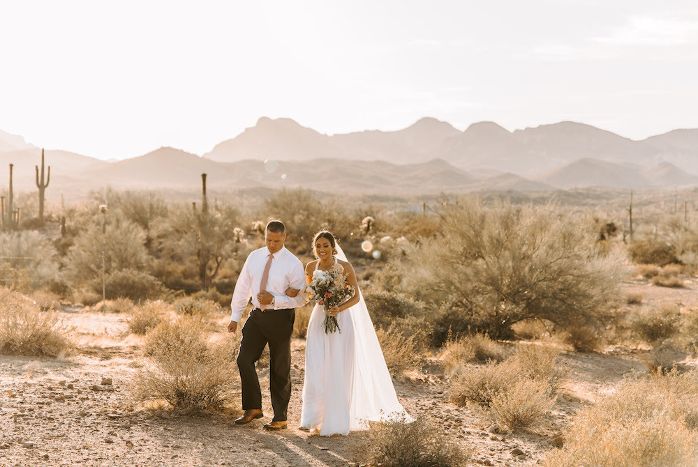 Bride walking arm-in-arm with her dad for down a trail for her Arizona desert elopement.