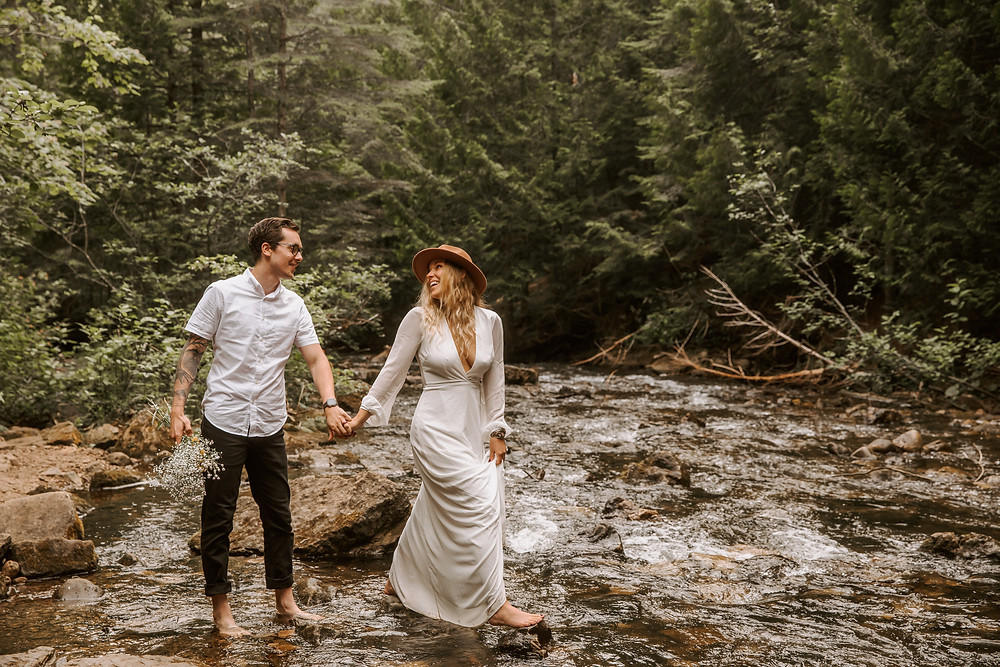 Bride and groom portrait walking through a stream at Miners Falls in MI.