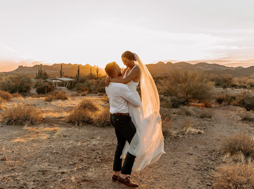 Groom holding up his bride in the middle of the Arizona desert after their intimate elopement.