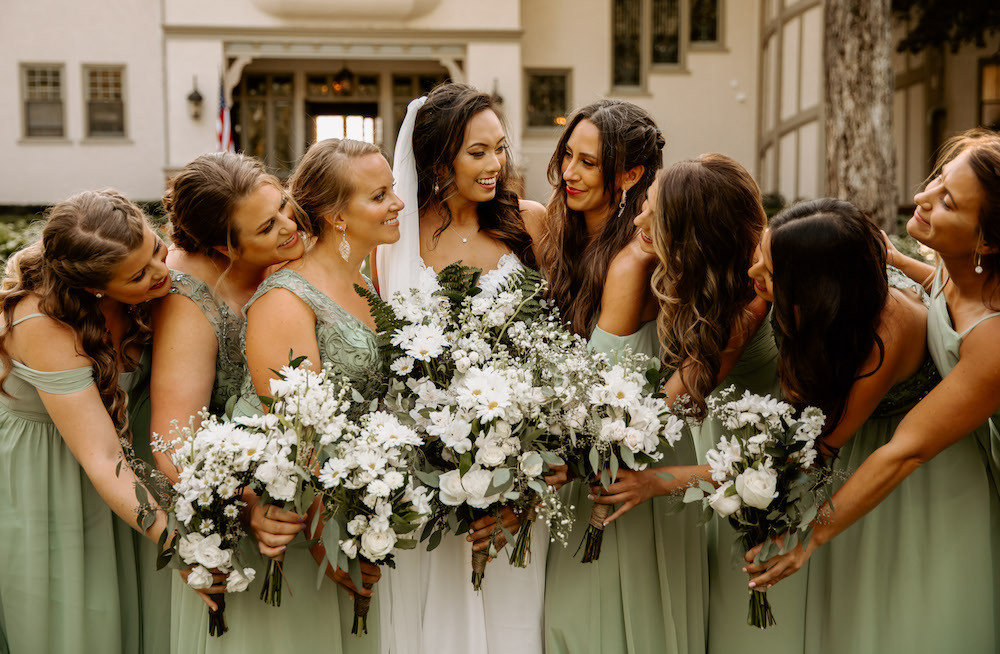 Bride and bridesmaids in seafoam green dresses with matching white and greenery floral bouquets.