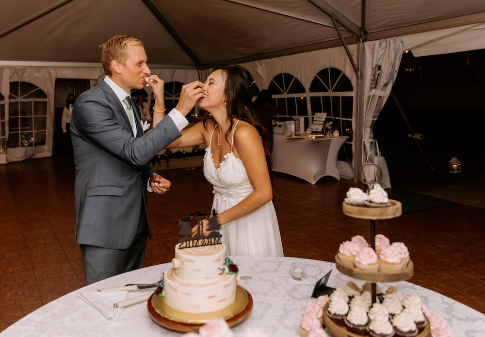 Bride and groom eating their first slice of wedding cake.