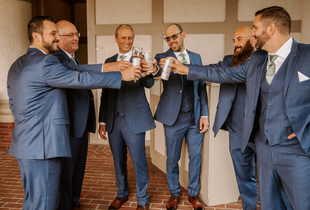 Groom and groomsman sharing a toast on the wedding day wearing blue tuxedos.