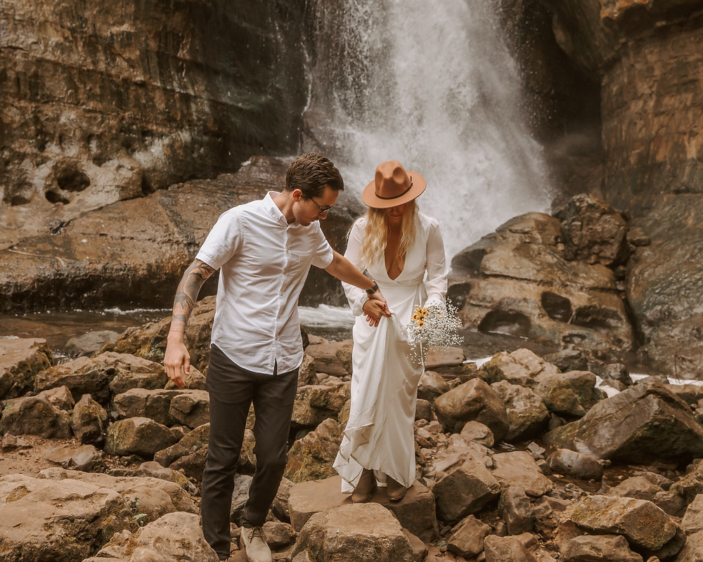 Bride and groom hiking after their elopement in Miners Falls, MI.