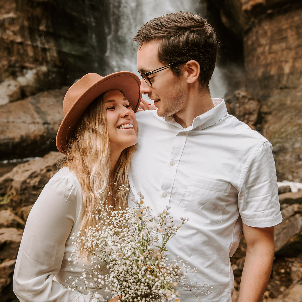 Bride holding her wildflower bouquet and groom standing in front of the Miners Falls waterfall in Michigan.