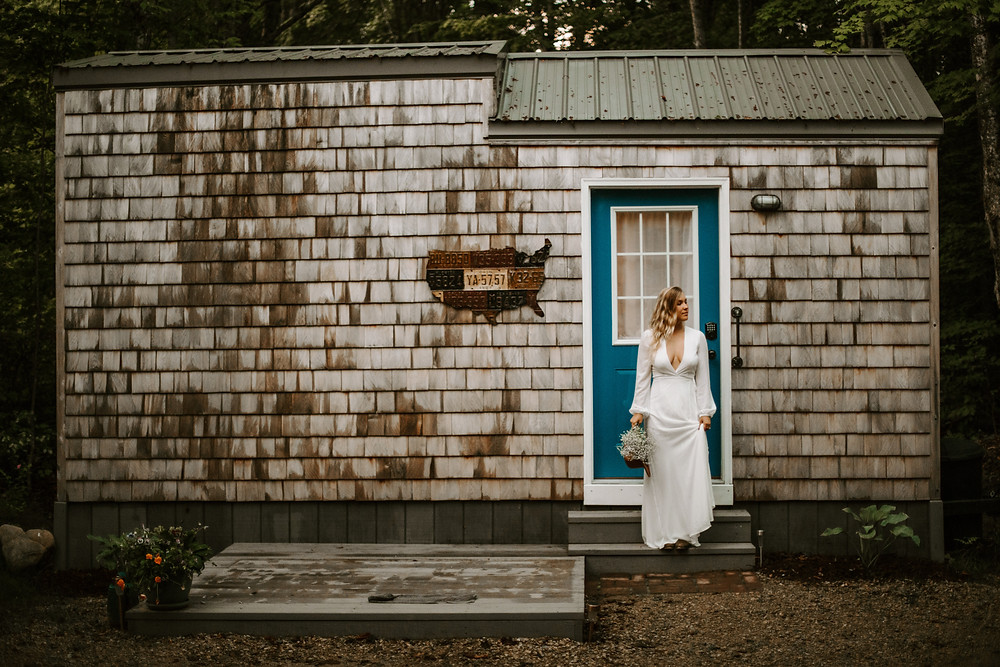 Bride standing in front of a rustic tiny home with a blue door in Michigan.