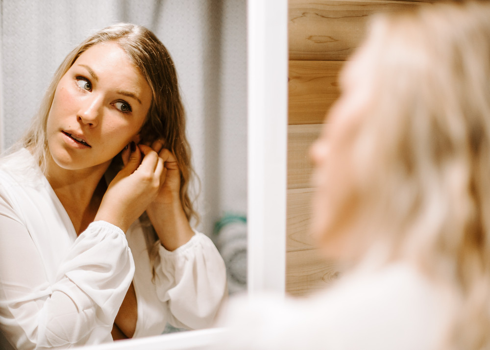 Bride getting ready in a tiny home, putting on her earrings.