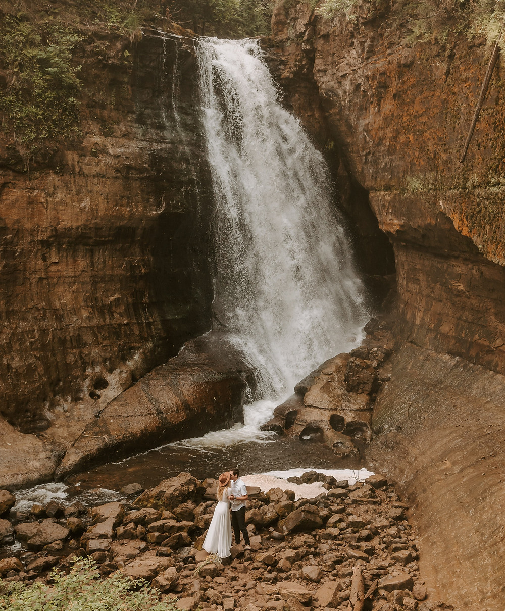 Bride and groom standing in front of the Miners Falls waterfall in Michigan after they eloped.