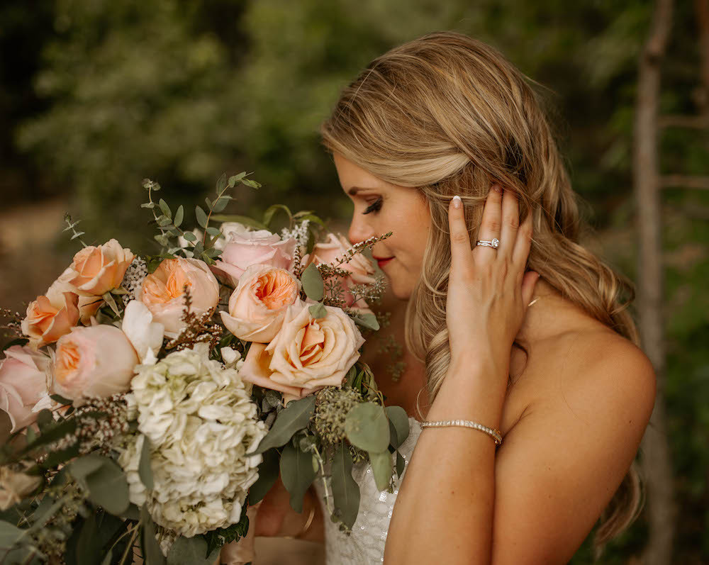 Bride holding her romantic summer wedding bouquet with pastel roses.
