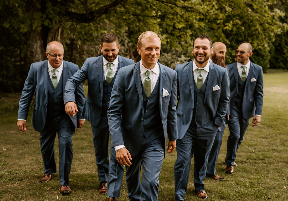 Groomsman wearing blue tuxedos and green ties with a white on the wedding day.