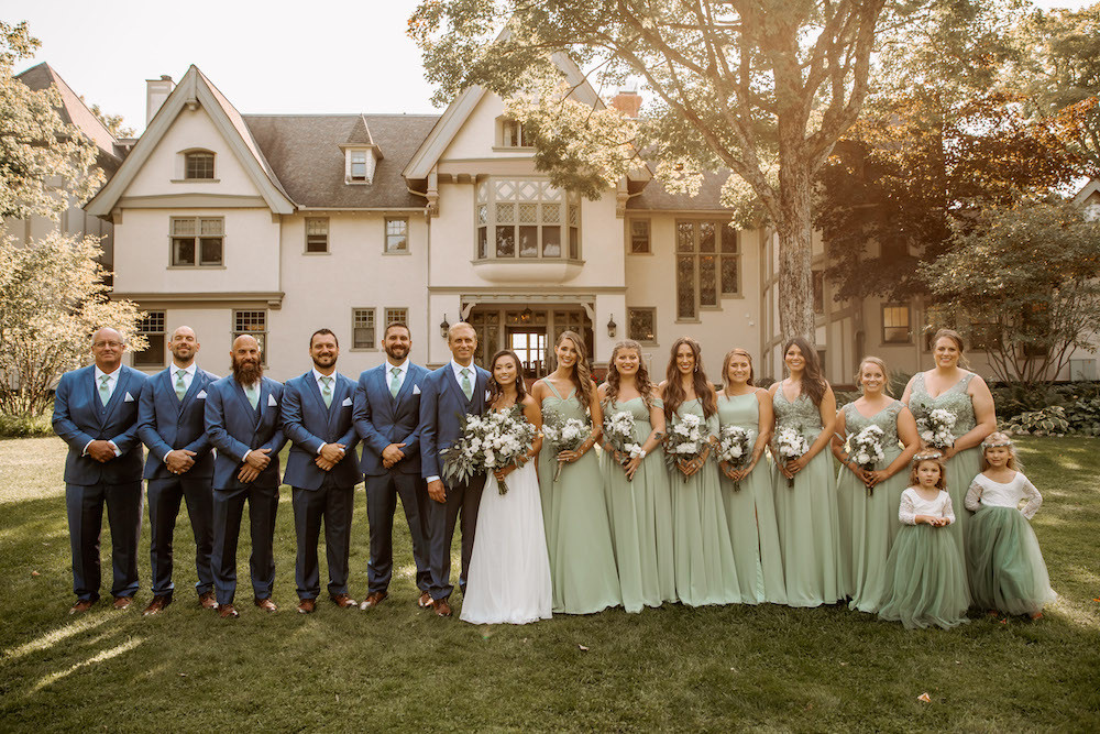 Bridal party photos with the men in blue tuxedos and the bridesmaids in long seafoam green dresses.
