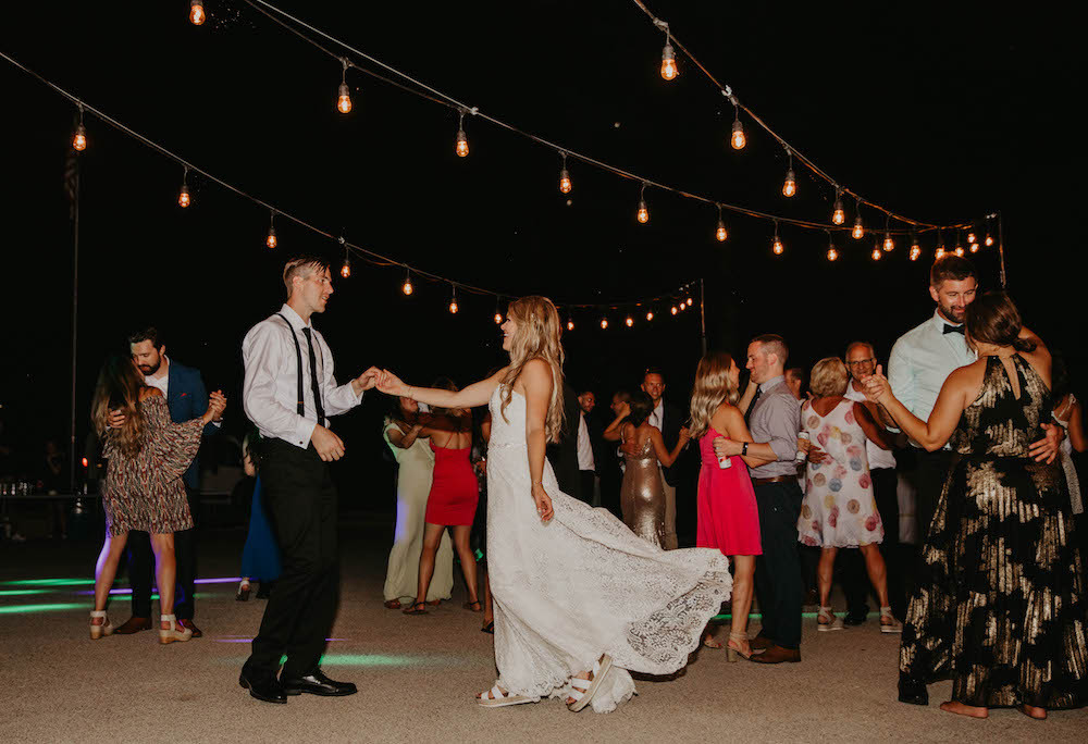 Bride and groom dancing at their reception under fairy lights in Michigan.