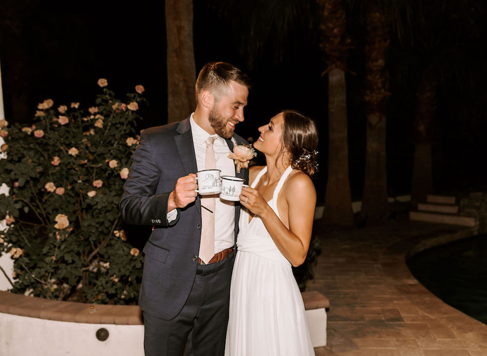 Bride and groom with their matching Mr. and Mrs. mugs having a toast after their elopement.