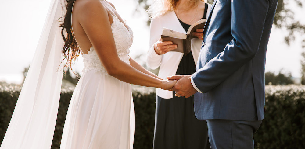 Bride and groom holding hands at the altar of their wedding ceremony.