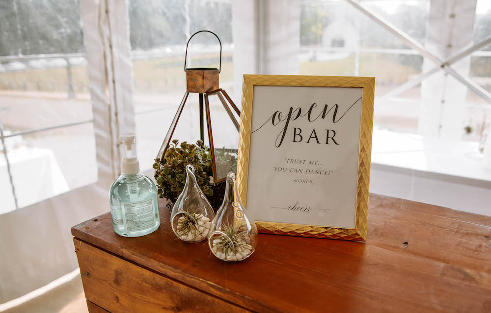 Custom open bar sign and wedding table details.