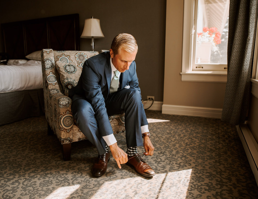 Groom getting ready photos wearing a navy blue suit and brown shoes.