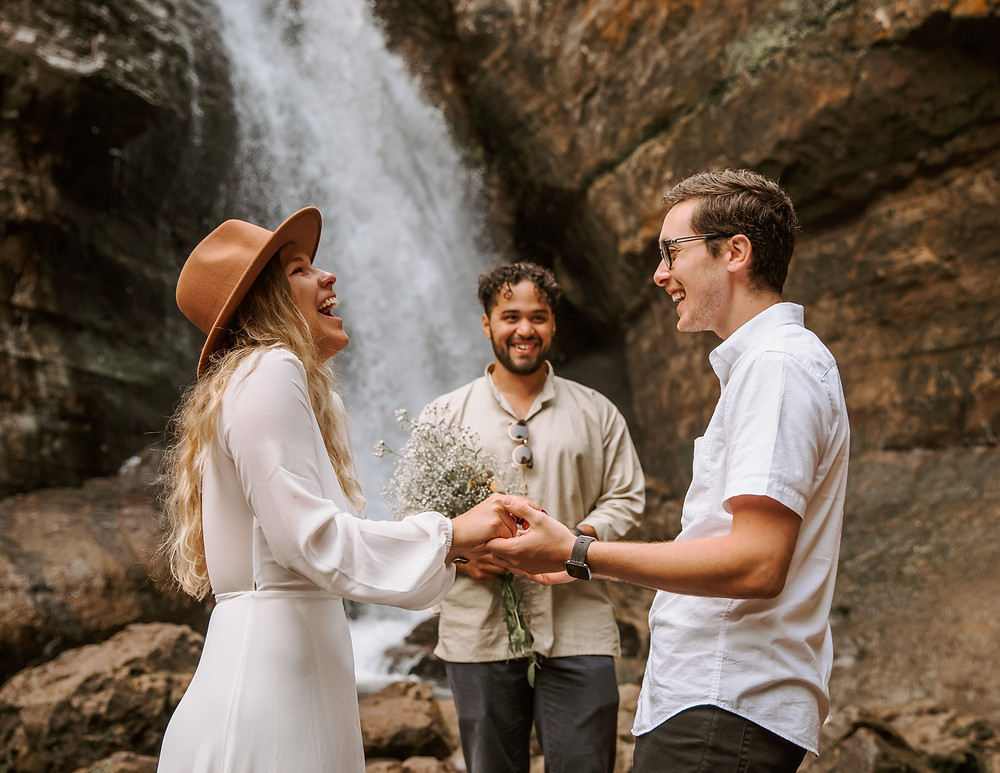 Bride and groom getting married in front of a waterfall with their officiant.